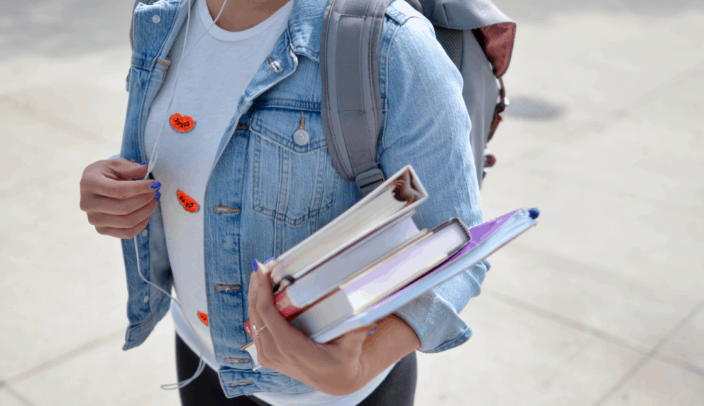 A College Student Holding Books In Hand